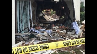Officials investigate after truck slams into apartment complex