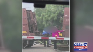 Train blocks road off Roosevelt Boulevard; people climb train to get through