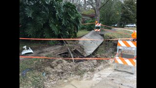 Sinkhole left behind after JSO officer crashes into fire hydrant during chase