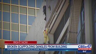Broken scaffolding dangles from building