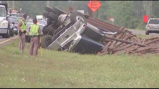 Photos: Log truck overturns in median in Nassau County