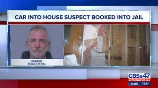 Car into house suspect booked into jail