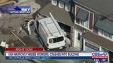 Van narrowly misses workers, crashes into building