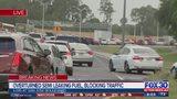 Overturned semi leaking fuel, blocking traffic